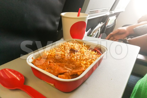 Simple in-flight meal of rice, meat, coffee in disposable utensils Stock Photo