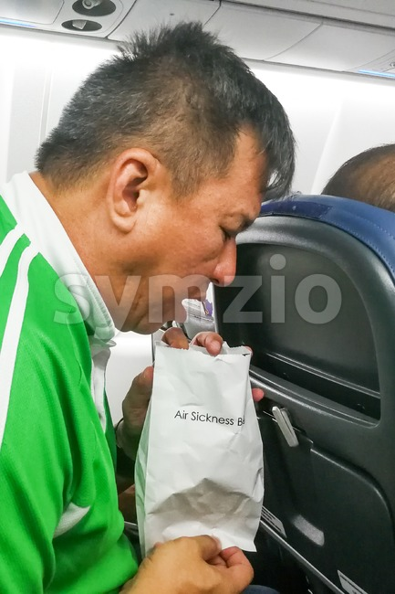 Nauseous air sickness Asian man vomiting into air sickness bag Stock Photo