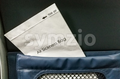 Air sickness bag tucked behind airplane seat pocket Stock Photo
