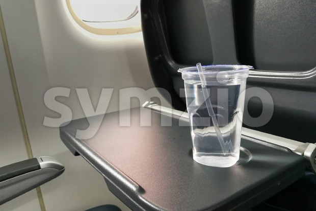 Disposable refreshing mineral water on table in air plane cabin Stock Photo