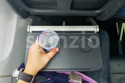 Hand holding disposable mineral water on table in air plane Stock Photo