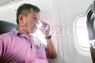 Person drinking water in airplane long haul flight to hydrate Stock Photo