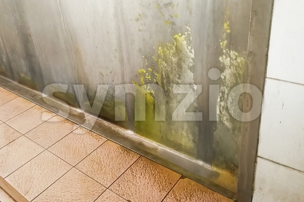 Unhygienic dirty urinal with limescale stain built up Stock Photo