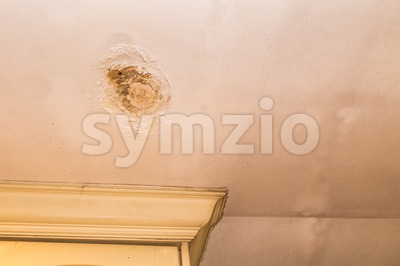 Roof leakages results damage ugly corrosion on plaster ceiling Stock Photo