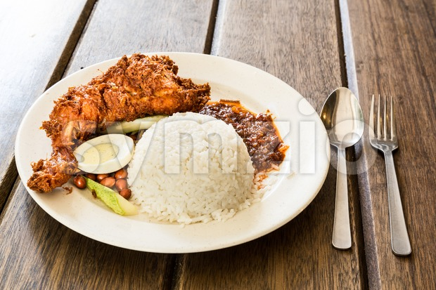Delicious Nasi Lemak with fried chicken on wooden table Stock Photo