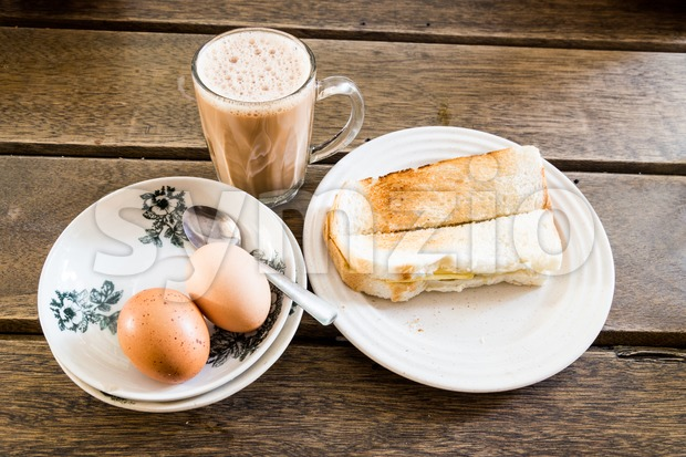 Popular Malaysian breakfast teh tarik, toast bread and half-boiled egg Stock Photo
