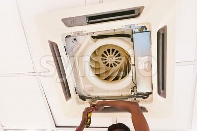 Technician servicing, maintaining and fixing a ceiling air conditioner cartridge Stock Photo