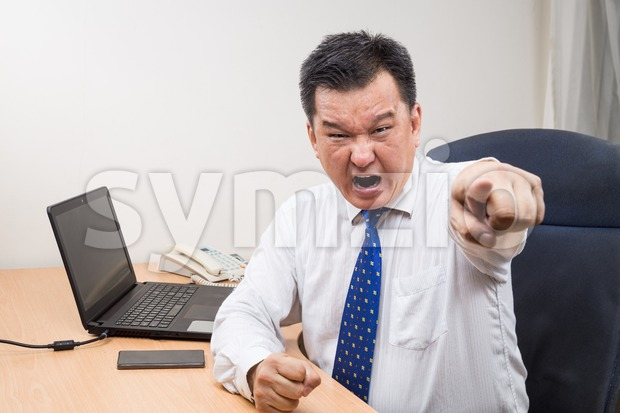 Angry and stressful Asian business manager shouting and pointing behind his desk in office