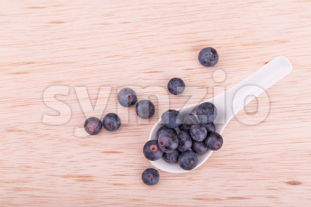 Healthy organic blueberries scooped in spoon on wooden surface