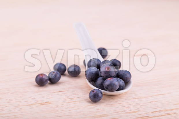 Organic blueberries scooped in spoon on wooden surface Stock Photo