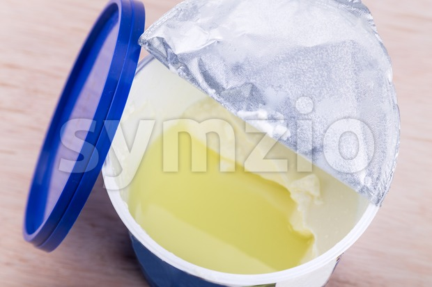 Layer of whey protein formed on top of packaged yogurt Stock Photo