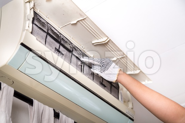 Technician pointing to air conditioner filter full of trapped dust Stock Photo