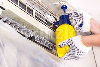 Technician spraying chemical water onto air conditioner grid to clean Stock Photo