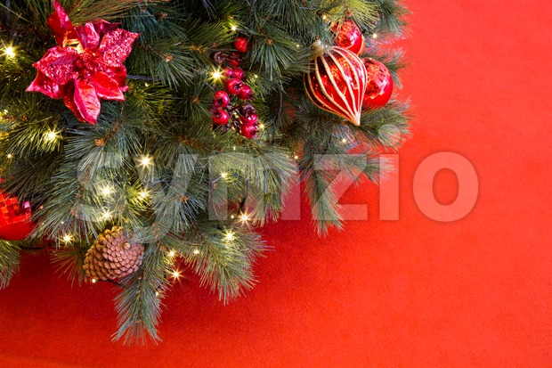 Decorated Christmas tree with sparkling lights on red backdrop Stock Photo