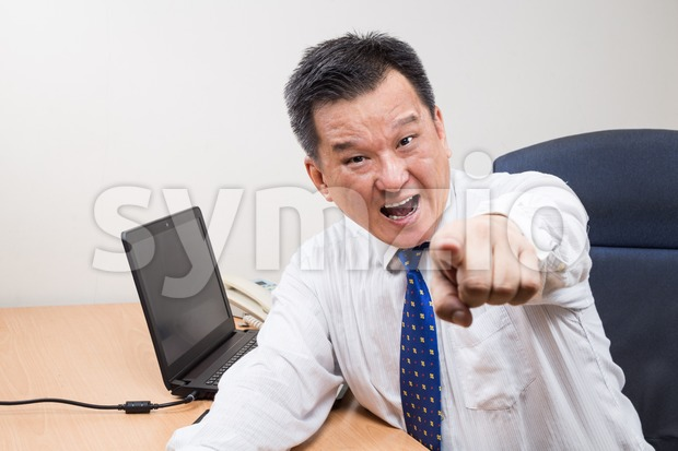 Angry and stressful Asian manager shouting and pointing in office Stock Photo