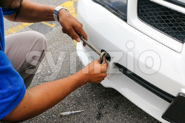 Mechanic fixing hook and chain onto car to tow Stock Photo
