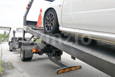 Car towed onto flatbed tow truck with hook and chain Stock Photo