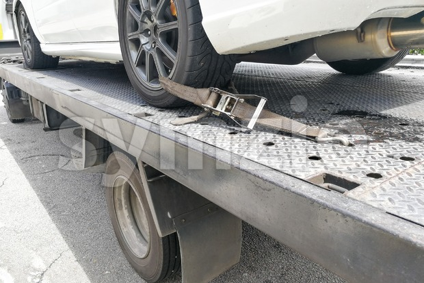 Car tire secured with safety belt on flatbed tow truck Stock Photo