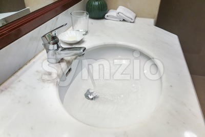 Modern hygienic wash basin with running water from tap faucet Stock Photo