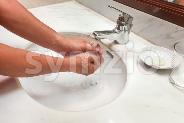 Person washing hands  with running water from tap faucet Stock Photo