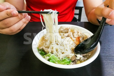 Person eating vermicelli pork noodle soup popular food, Penang Malaysia Stock Photo