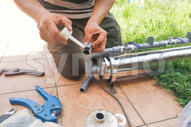 Series of plumber fixing up ourdoor water filter with pvc piping Stock Photo
