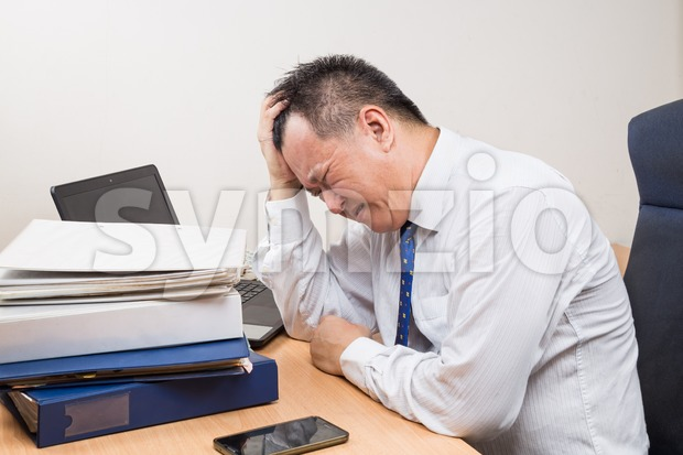Frustrated and stressful Asian business manager behind desk in office Stock Photo