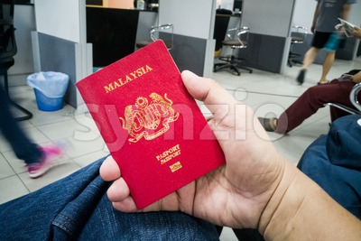 Person holding Malaysia international passport Stock Photo