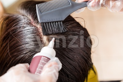 Hair dresser applying chemical hair color dye onto hair roots Stock Photo