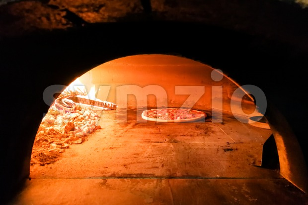 Italian pizza being baked in traditional wood flame fire oven at restaurant