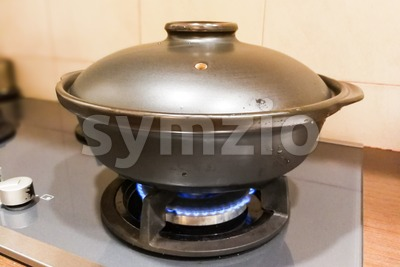 Ceramic clay pot on gas fire generated stove Stock Photo