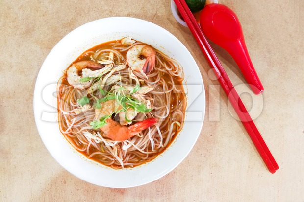 Overhead view of authentic delicious Sarawak Laksa vermicelli with big prawns