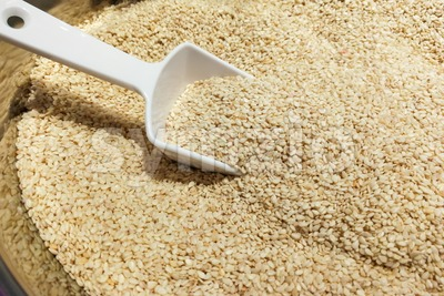 Heap of white sesame seeds with ladle Stock Photo