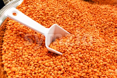 Heap of organic red dal with ladle in bucket Stock Photo