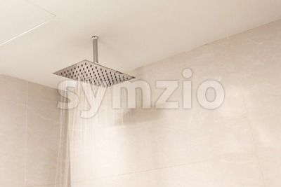 Shower head with refreshing water droplets spray in bathroom Stock Photo