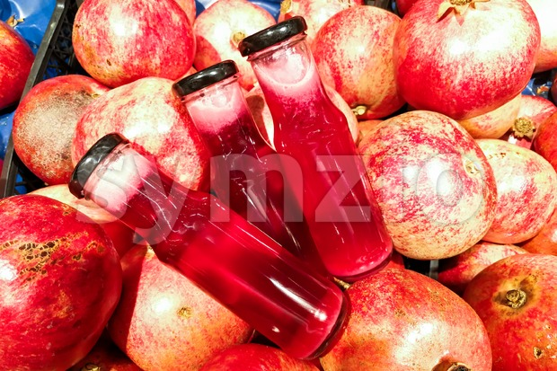 Fresh cold pressed organic pomegranate juice in bottle against heap of pomegranate fruits