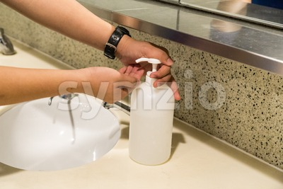 Person applying anti bacterial hand wash liquid onto hands Stock Photo