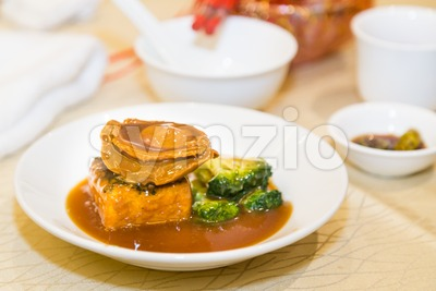 Braised abalone with broccoli and beancurd, premium expensive Chinese delicacy Stock Photo