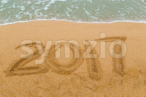 2017 inscription written on sandy beach with wave approaching Stock Photo