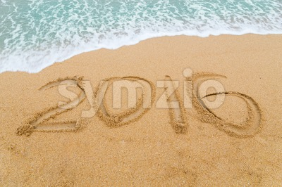 2016 inscription written on sandy beach with wave approaching Stock Photo