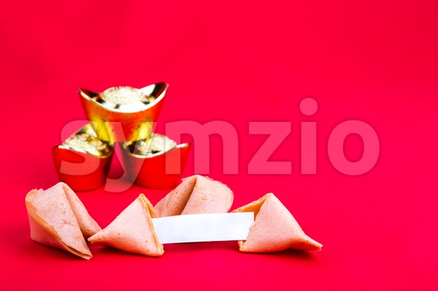Chinese fortune cookies with decorative gold nuggets and blank predictive label on red background