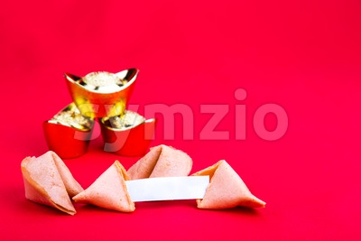 Fortune cookies with decorative gold nuggets on red background Stock Photo