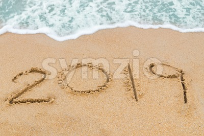 2019 inscription written on sandy beach with wave approaching Stock Photo