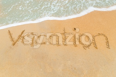 VACATION inscription written on sandy beach with wave approaching Stock Photo
