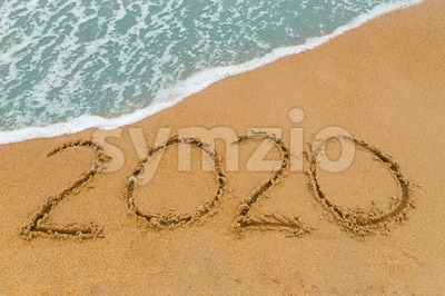 2020 inscription written on sandy beach with wave approaching Stock Photo