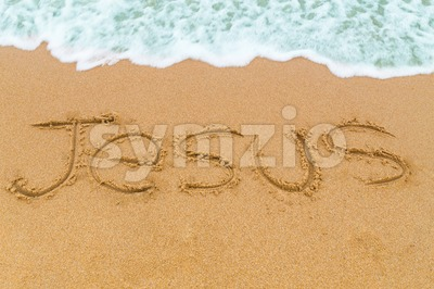 JESUS inscription written on sandy beach with wave approaching Stock Photo