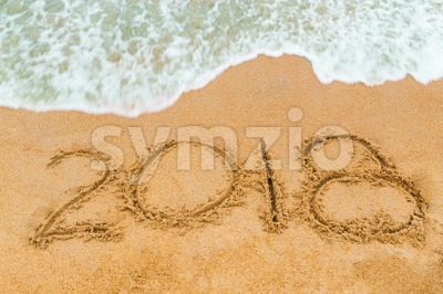 2018 inscription written on sandy beach with wave approaching Stock Photo