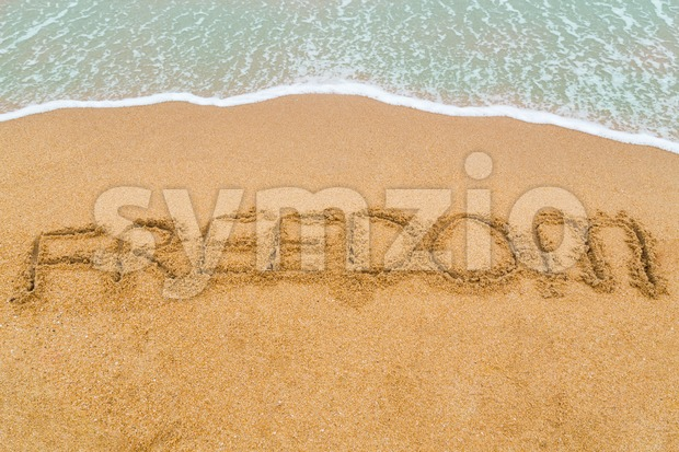 FREEDOM inscription written on sandy beach with wave approaching Stock Photo