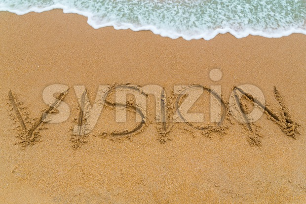 VISION inscription written on sandy beach with wave approaching Stock Photo