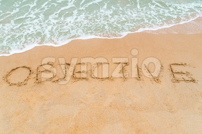 OBJECTIVE inscription written on sandy beach with wave approaching Stock Photo